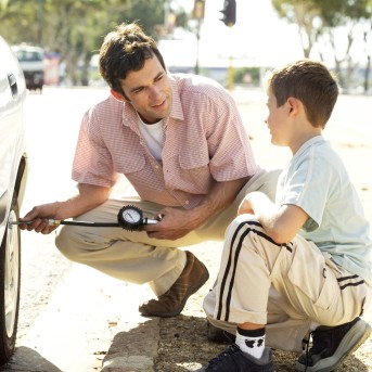 Young Man Checking the Air Pressure of Car Tire with His Son